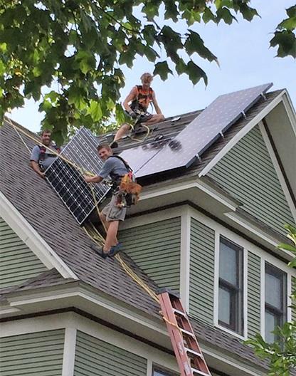 تعداد مرد در حال نصب پنل خورشیدی بر روی سقف شیبدار