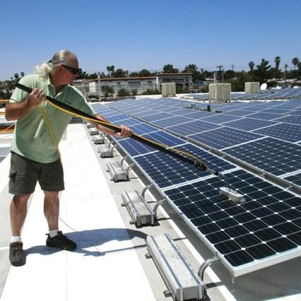 مردی در حال تمیز کردن و نگهداری پنل خورشیدی